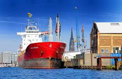 Der Stückgutfrachter Aquila Companion im Steinwerderhafen - historische Hafenarchitektur; Kirchturm der NIkolaikirche im Hintergrund.