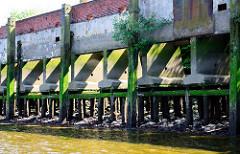 Kaimauer bei Niedrigwasser im Hamburger Hafen - Betonstützen der Kaianlage sind auf Eichenstämmen gegründet; Melniker Ufer / Moldauhafen.