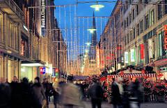 Hamburger Weihnachtsmarkt in der Spitaler Strasse - Lichterketten hängen über der Fussgängerzone / Einkaufsstrasse - Passanten bummel zwischen den bunten Marktbuden.