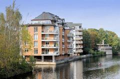 Moderne Wohnhäuser am Alsterkanal in Hamburg Eppendorf - ein Kajakfahrer fährt sein Kajak auf der Alster.