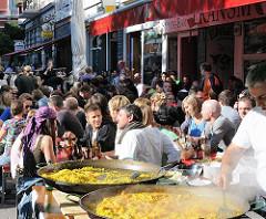 Pfannen mit Reisgerichten werden am Schulterblatt zubereitet. Gäste sitzen an Tischen in der Sonne auf der Strasse.