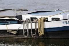Binnenschiff am Ufer der Süderelbe von Hamburg Harburg - die Taue liegen aufgeschossen über der Bordwand des Schiffs.