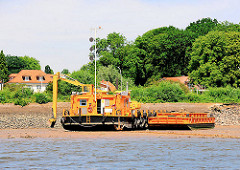 Ein Arbeitsboot liegt bei Ebbe auf dem trockengefallenen Ufer der Elbe vor Hamburg Nienstedten.