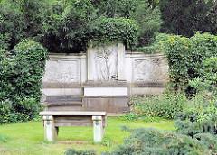 Grabstein mit figürlichen Relief mit Efeu bewachsen - steinerne Ruhebank vor dem Grab.