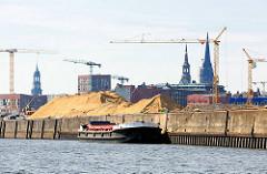 Arbeitsschiff an der Kaianlage des Versmannkai im Baakenhafen - Kirchtürme der Hansestadt Hamburg im Hintergrund.