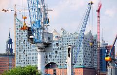 Hafenkräne vor der Baustelle der Elbphilharmonie in der Hamburger Hafencity.
