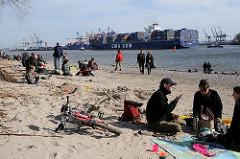 Elbstrand vor Hamburg Othmarschen - Hamburger und Hamburgerinnen sitzen auf Decken oder gehen im Sand spazieren - Containerschiff auf der Elbe.