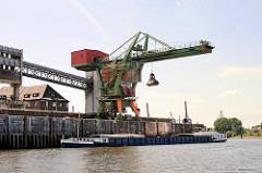 Krananlage am Kalikai im Wilhelmsburger Reiherstieghafen. Die Ladung eines Binnenschiffs wird mit einem Greifer aus dem Laderaum geholt.