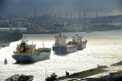 Regenwetter in Hamburg - der Himmel ist schwarz; drei Schiffe, die im Elbstrom an den Dalben liegen, werden von der Sonne angestrahlt.