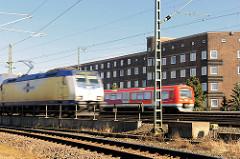 Fahrender Metronomzug und  S - Bahn auf den Gleisen auf der Veddel - Bahnstrecke am Wohngebiet; Klinkerhäuser auf der Hamburger Veddel.