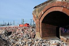 Abriss der aus Ziegelsteinen gemauerten historischen Pfeiler-Bahnstrecke an der Versmannstrasse - im Hintergrund fährt ein Regionalzug mit rotem Triebwagen. (2008)