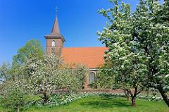 Blauer Frühlingshimmel - blühende Bäume, Osterglocken auf der Wiese - St. Pankratiuskirche von Hamburg Neuenfelde, Bezirk Harburg.