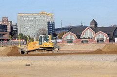 Bauarbeiten in der Hamburger Hafencity - ein Bagger planiert eine Sandebene; im Hintergrund die Deichtorhallen am Oberhafen und die City Hochhäuser am Klosterwall.