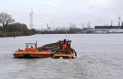 Eine Barkasse schleppt eine mit Hafenschlick beladene Schute im Finkenwerder Köhlfleet zur Saugerstaion und Schlickdeponie im Finkenwerder Vorhafen.