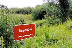 Schild des Baches Tarpenbek in Hamburg Niendorf - Wiesen am Ufer der Tarpenbek.