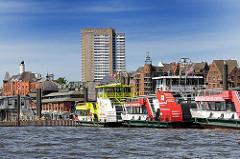 Hafenfähren am Anleger am Hafenrand. Im Hintergrund Architektur von Hamburg Altona.