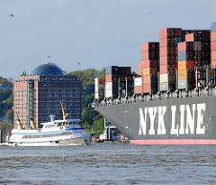 Ein Containerschiff läuft aus dem Hamburger Hafen aus - im Hintergrund das ehem. Kühlhaus, jetzt Seniorenresidenz an der Elbe in Hamburg Ottensen.