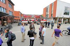Areal der alten Rinderschlachthalle in Hamburg St. Pauli - auf einer Stufentribüne sitzen AnwohnerInnen und überblicken den Platz.