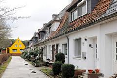Reihenhäuser in Hamburg Hausbruch - im Hintergrund ein Einzelhaus mit gelber Fassade.
