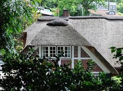 Reetdachhaus mit Fachwerk - Ziegelfassade; umgeben von Bäumen.