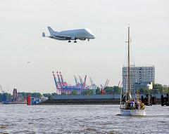 Anflug eines Beluga Transportflugzeugs auf den Airbusflughafen in Hamburg Finkenwerder - im Hintergrund Containerkräne am Waltershofer Hafen.