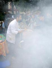 Kulinarische Angebote -  Fest auf der Schanze - von einem Grill steigt dichter Qualm auf.