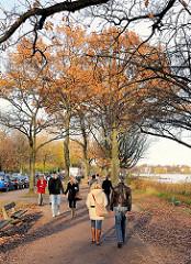 Sonniger Herbst in Hamburg Rotherbaum - Spaziergänger an der Aussenalster auf dem Alsterwanderweg.