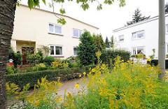 Wohnhäuser in Wandsbek Gartenstadt die ab 1910 entstand - am Strassenrand blühen Blumen und Wildkraut.