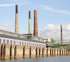 Kaimauer und Neubauten am Müggenburger Kanal - Fabrikschornsteine auf der Peute in Hamburg Veddel.