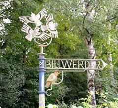 Kunstvoll gestaltetes Hinweisschild zu Lohbrügges Nachbarstadtteil Hamburg Billwerder.