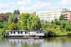 Hausboot am Billeufer in Hamburg Hamm - Grünanlage, Wohnblocks im Hintergrund.