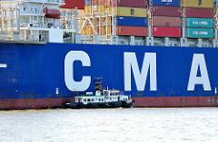Ein Lotsenboot legt an einem Containerfrachter mitten auf der Elbe an; das Frachtschiff verlässt den Hamburger Hafen.