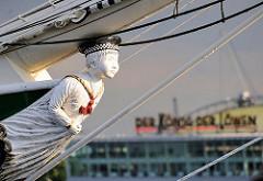 Gallionsfigur des Museumsschiffs Rickmer Rickmers im Hamburger Hafen an den St. Pauli Landungsbrücken - im Hintergrund das Zelt des Musicals Der König der Löwen.
