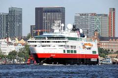 Das Kreuzfahrtschiff FRAM läuft aus dem Hamburger Hafen aus - im Hintergrund Hochhäuser von Hamburg St. Pauli.