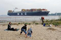 Kinder spielen im Sand an der Elbe - ein Containerfrachter hat den Hamburger Hafen verlassen und fährt elbabwärts Richtung Nordsee.