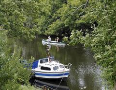 Dove-Elbe bei Hamburg Reitbrook - Sportboot am Ufer - Kanu auf dem Wasser des Hamburger Flusses.