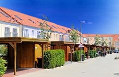 Neubauten in Hamburg Rönneburg - einstöckige Reihenhäuser - Carports aus Holz vor den Wohngebäuden.