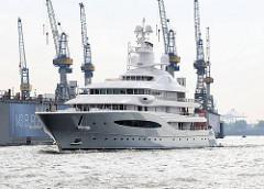 Die 92m lange Privatyacht MAYAN QUEEN IV läuft in den Hamburger Hafen ein - Werftkräne der Werft Blohm und Voss, wo das Luxusschiff 2008 gebaut wurde.