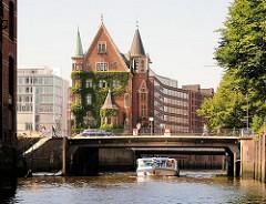 Barkasse der Hamburger Hafen- und Fleetrundfahrt in der Speicherstadt - re. im Hintergrund Neubauten neben dem historischen Speichergebäude.