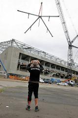 Ein Kran hebt ein Teil des Tribünendachs auf den Stadtionbau vom Fussballverein St. Pauli - ein St. Pauli Fan fotografiert die Aktion.
