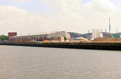 Baustelle und Lagergebäude beim Versmannkai / Baakenhafen - Kirchenpauerkai; im Hintergrund die Hamburger Freihafenelbbrücken über die Norderelbe.