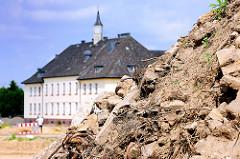 Schuttberg auf dem Gelände der ehem. Lettow Vorbeck Kaserne in Hamburg Jenfeld - im Hintergrund das Hauptgebäude mit Uhrenturm.