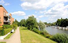 Uferweg mit Grünanlage an der Bille in Hamburg Hamm - Wohnhäuser am Wasser; Sportboote im Sportboothafen Hamburg Rothenburgsort / Billhuder Insel.