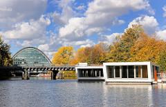Hochwasserbassin Hamburg Hammerbrook -  Schwimmende Häuser, Hausboote - wohnen auf dem Wasser. Im Hintergrund das Bürogebäude Berliner Bogen; Herbstbäume, blauer Himmel - weisse Wolken.