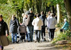 Der Herbstwald in Hamburg Niendorf als Ausflugsziel am Sonntag - Nordic Walking und Jogger auf dem Waldweg in der Sonne.