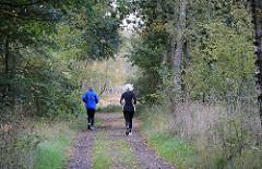 Jogger auf einem Waldweg im Duvenstedter Brook.