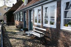 Wohnen an der Elbe in Oevelgoenne - Ruhebank auf Kopfsteinpflaster vor dem Lotsenhaus.