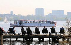 Frühlingssonne in Hamburg an der Aussenalster - ein Alsterschiff fährt Richtung Krugkoppelbrücke - sonnenhungrige Hamburger_innen sitzen in Stühlen auf dem Bootssteg an der Rabenstrasse.