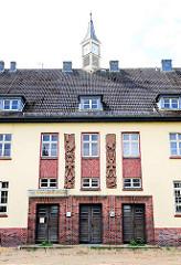 Eingangsbereich mit militaristischem Wandschmuck über den Türen - Hauptgebäude der ehem. Lettow Vorbeck Kaserne in Hamburg Jenfeld.