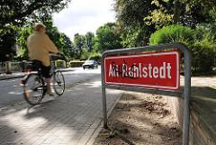 Ortsteilschild Alt Rahlstedt -  Fahrradfahrerin auf dem Gehweg der Oldenfelder Strasse.